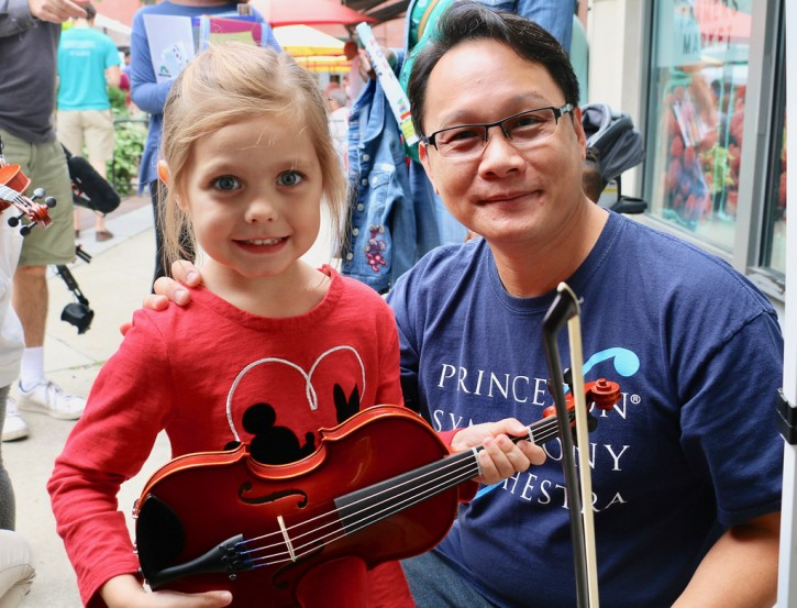 Girl holding violin with PSO musician