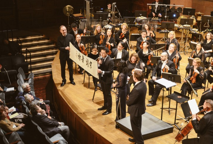 Rossen Milanov and composer Zhou Tian hold the Chinese scroll presented to the PSO following the performance of Broken Ink.