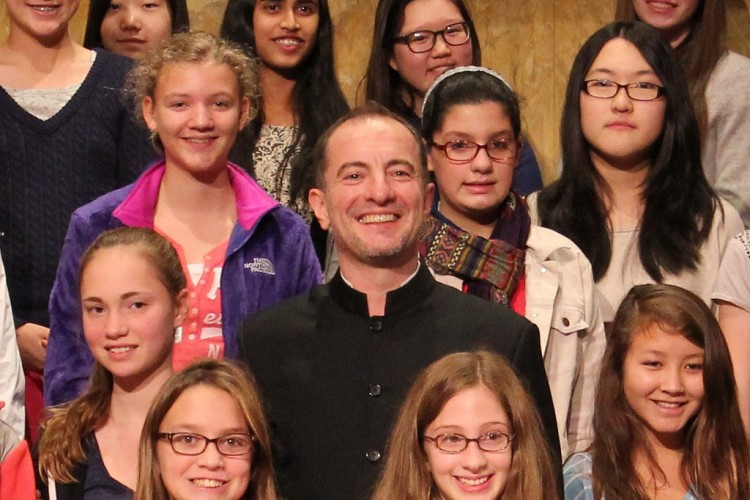 Rossen Milanov surrounded by middle school students onstage on risers.