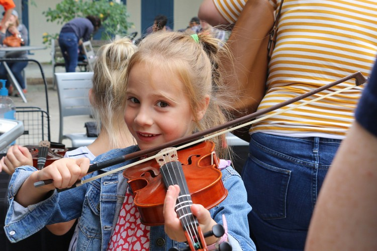 Smiling girl trying out violin
