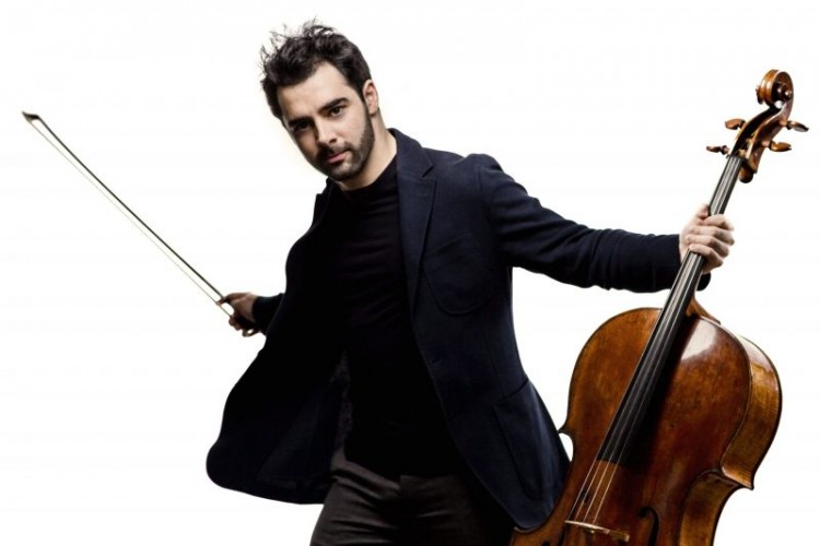 Pablo Ferrández looking directly at the camera with arms spread out. In his left hand he holds a cello. In his right hand, he holds the bow.