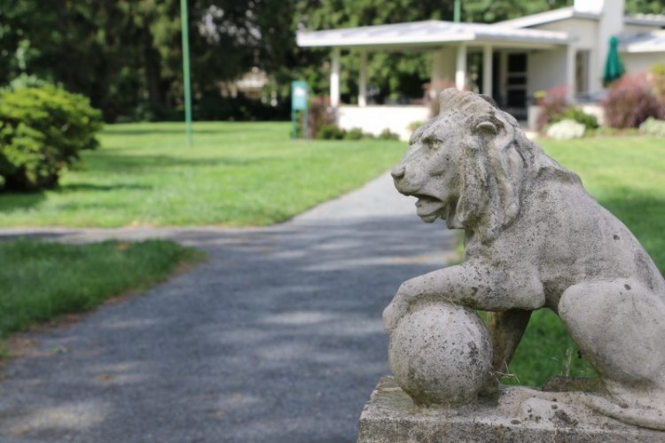 A gravel pathway through a lawn leading up to a building with an open porch. A statue of a lion is next to the pathway.