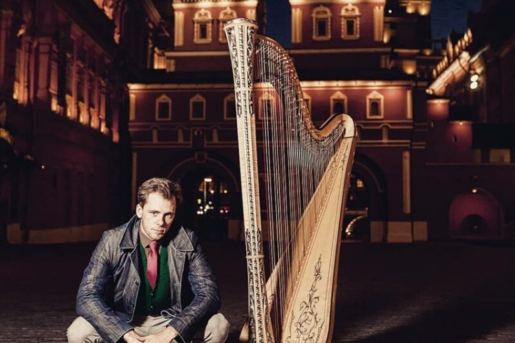 Alexander Boldachev poses crouched on the ground next to a harp. It's nighttime. Boldachev and the harp are in front of a lit up building.