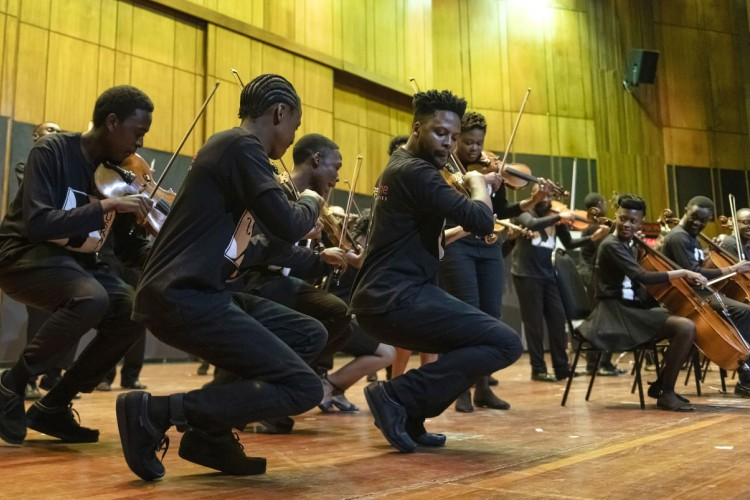 Violinists in the Buskaid Soweto String Ensemble performing, viewed in profile. Other performers with string instruments are visible in the background.