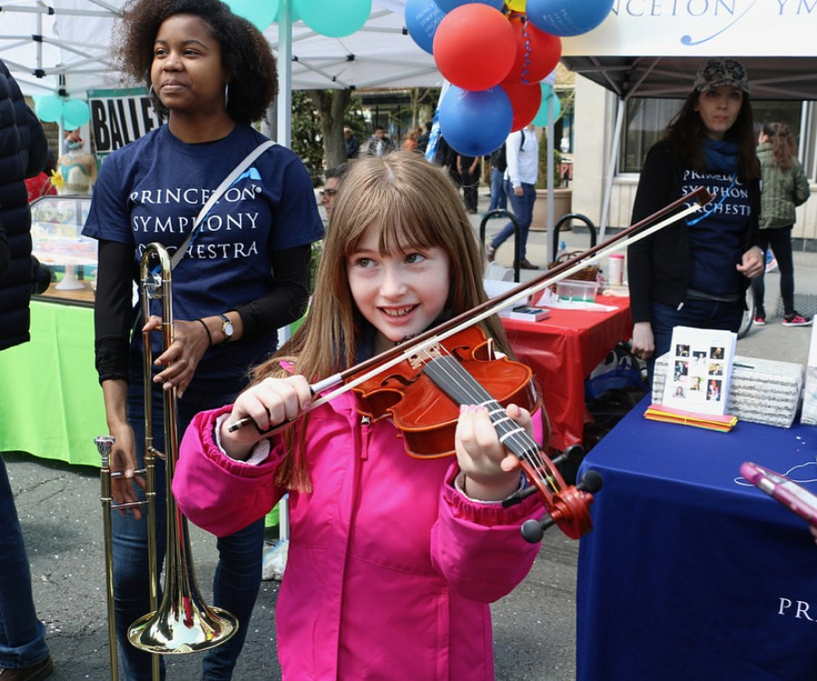Girl trying out a violin at the PSO BRAVO! Instrument Petting Zoo