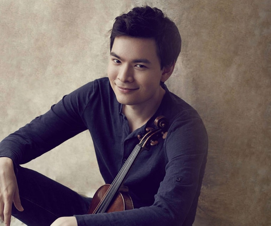 Stefan Jackiw sitting against a wall with his violin