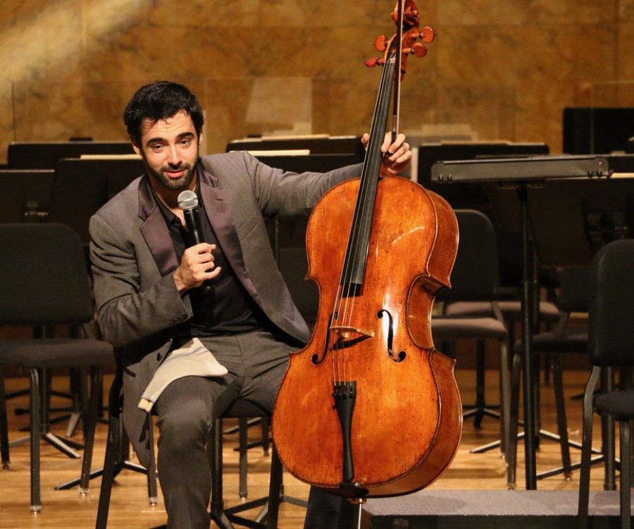 Pablo Ferrández, seated on-stage, holding a cello and speaking into a microphone