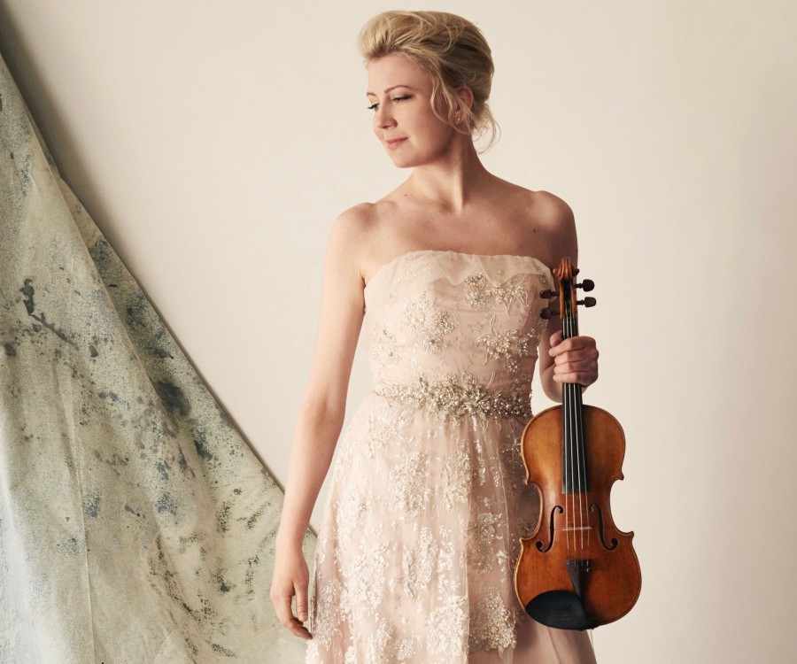 Elina Vähälä in concert dress holds her violin.