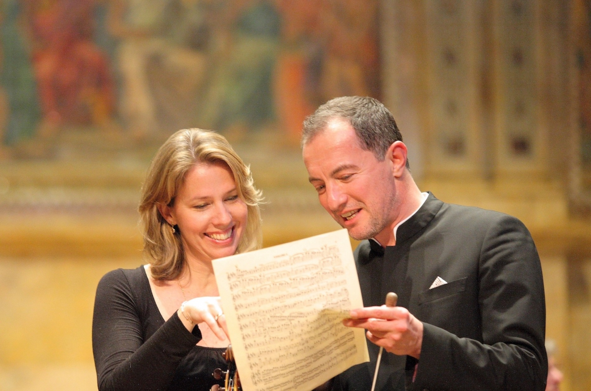 A female violinist and male conductor smile as they look over a page of music