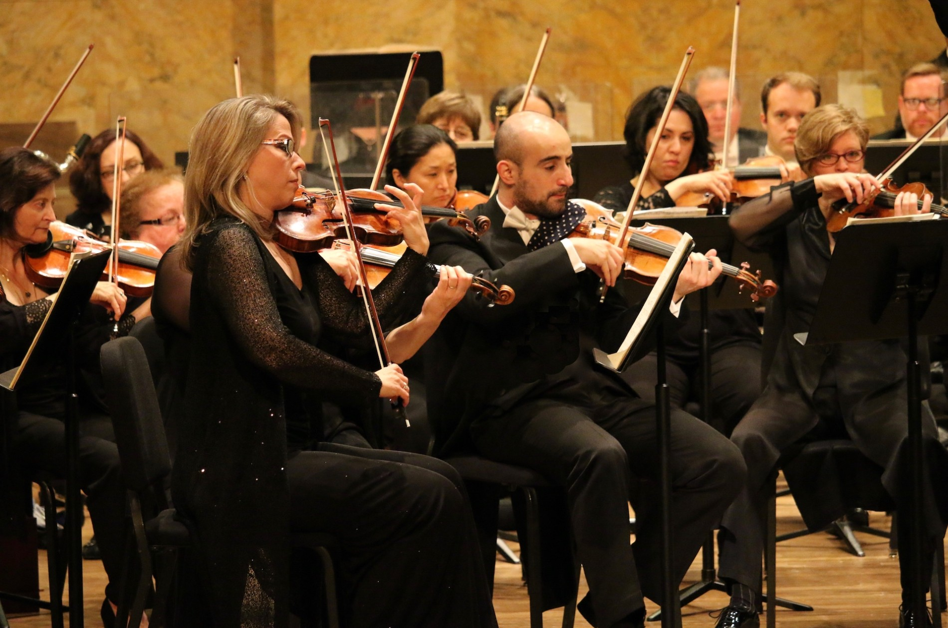 PSO violinists playing onstage in concert black