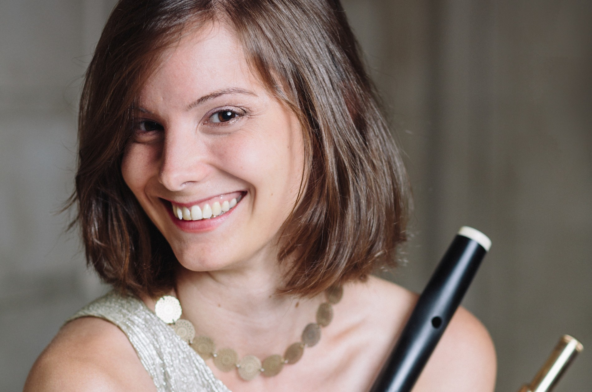 Arrayed in gold, Melanie Williams holds early and modern flutes