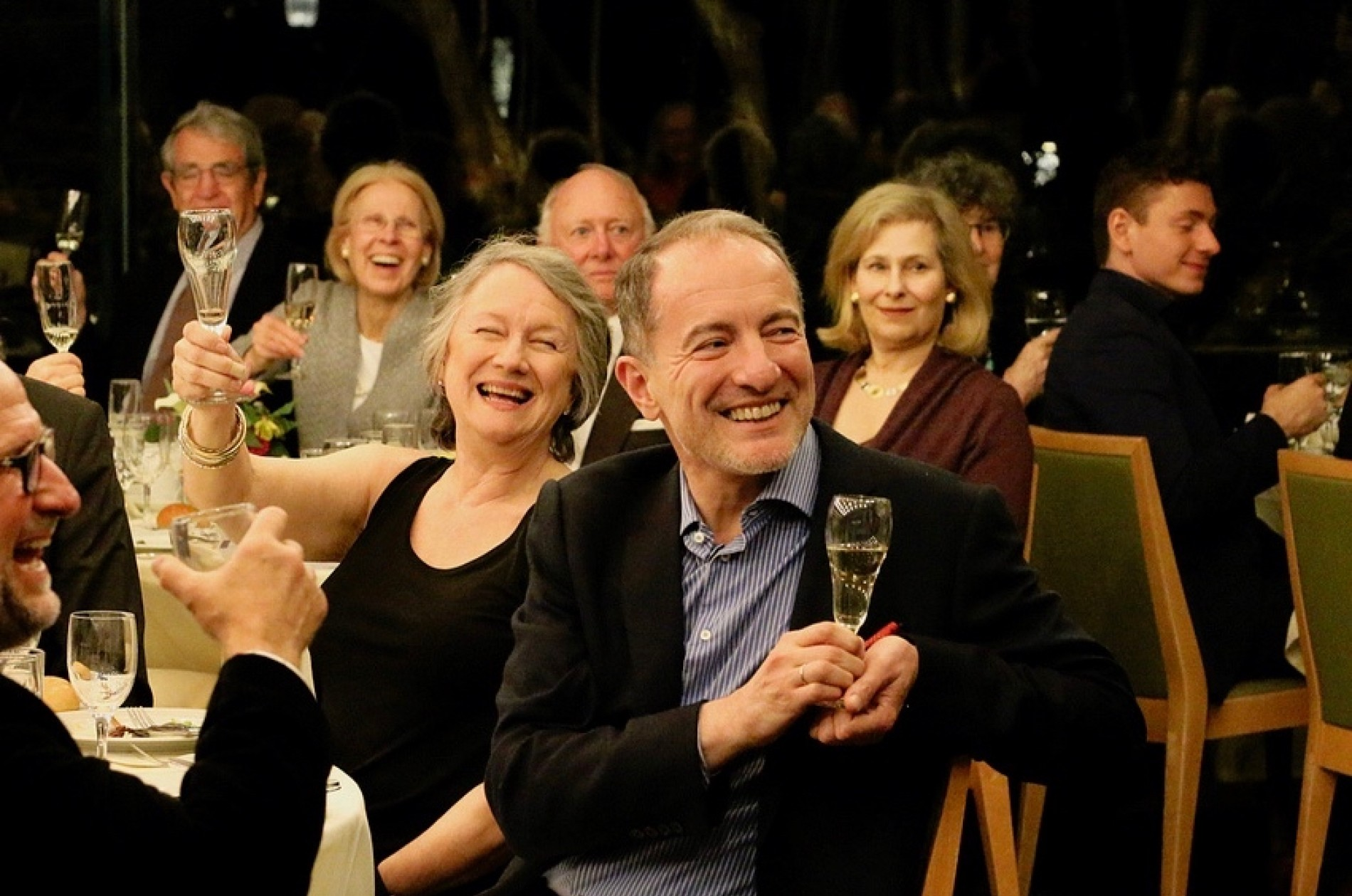 Sponsors toasting Rossen Milanov while seated at a dinner