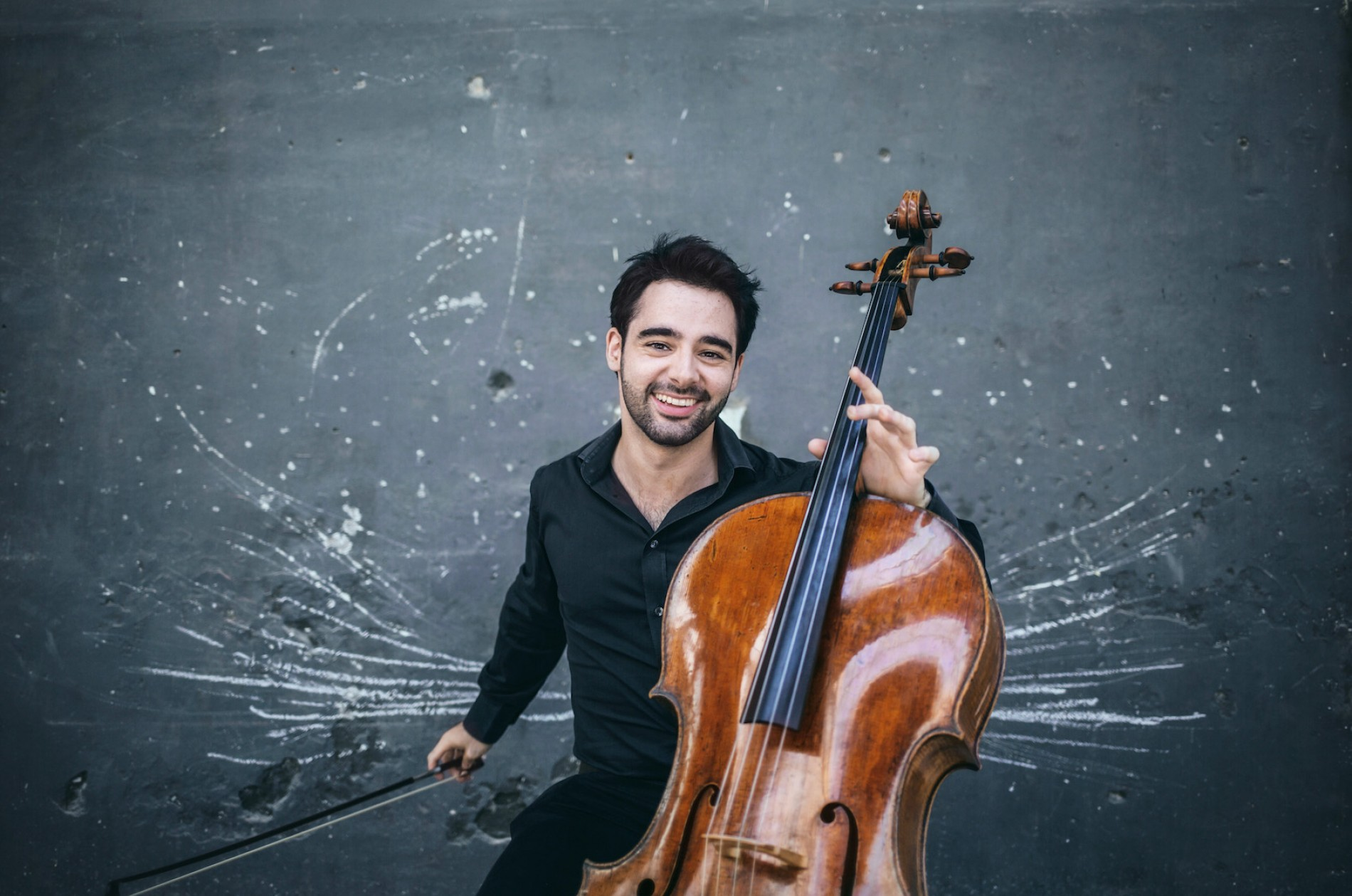 Pablo Ferrández holds his cello up in front of a spatter-patterned wall.