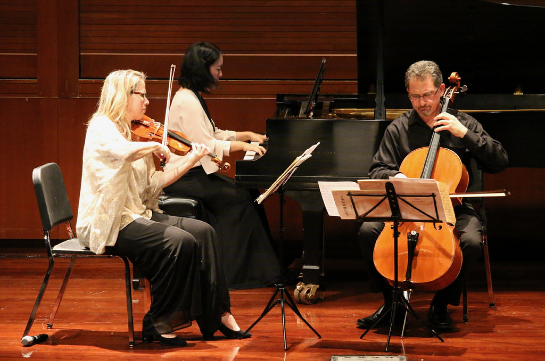 A chamber trio featuring a violinist, a pianist, and cellist performing onstage.
