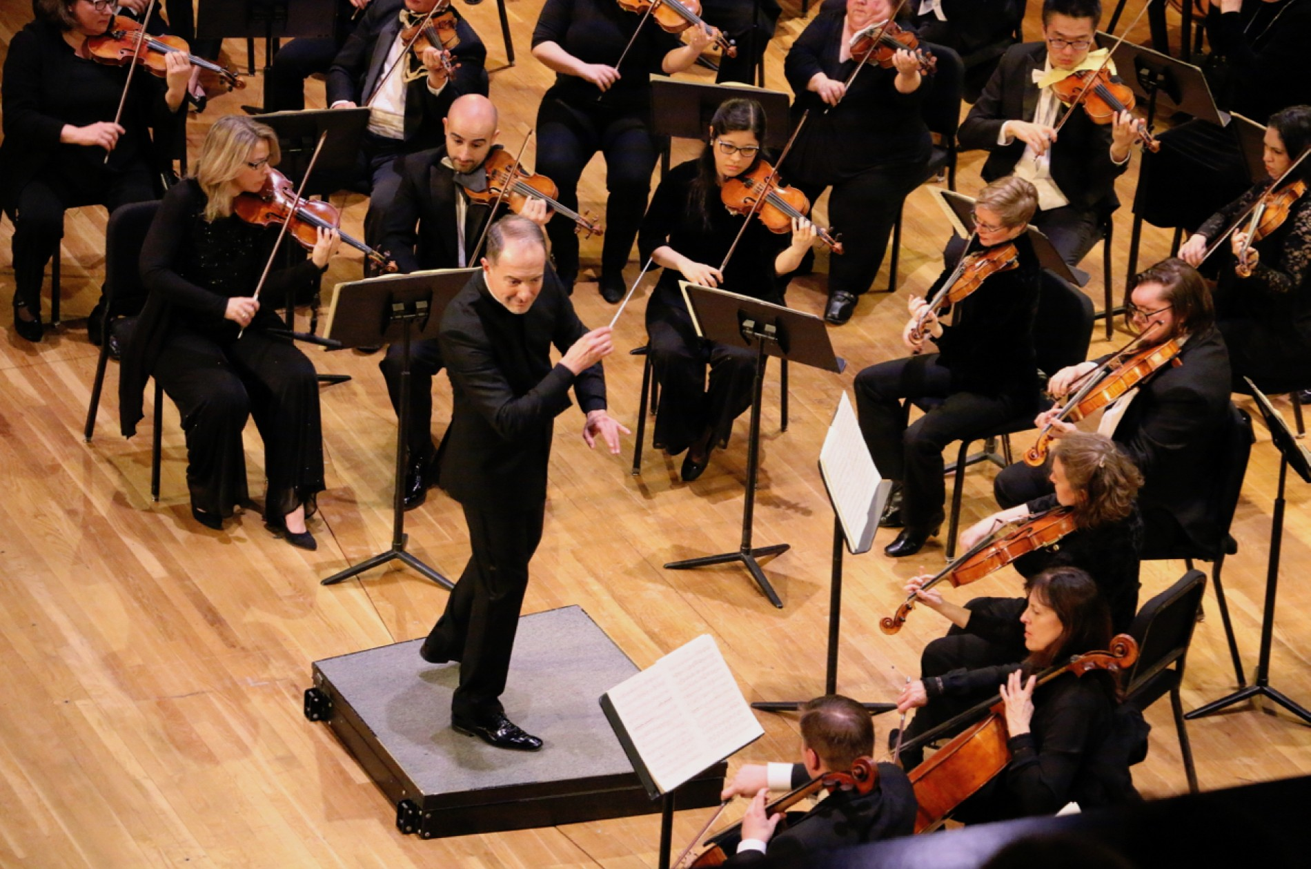 Rossen Milanov conducts the PSO in concert; everyone wears concert black.