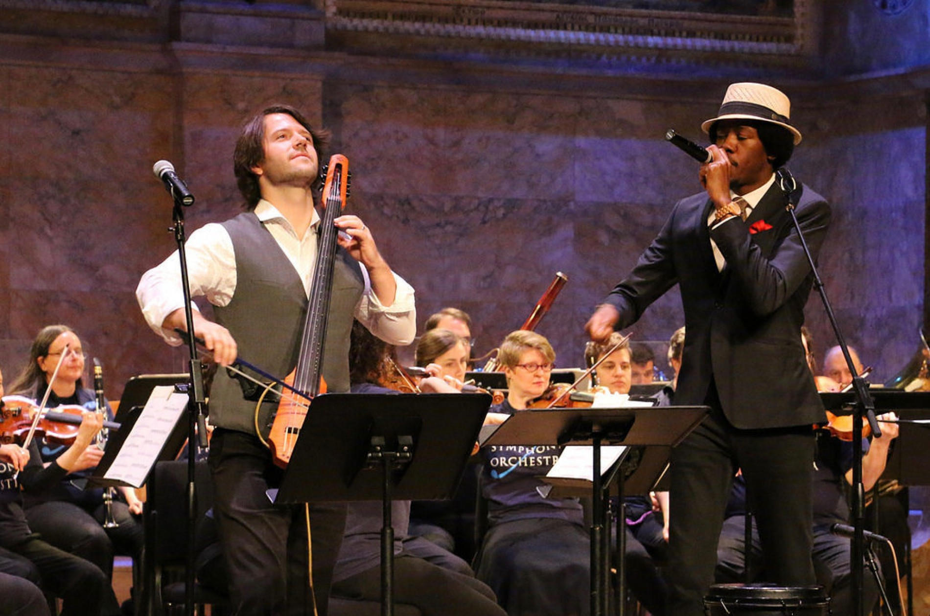 An electric cellist and beat boxer play onstage with orchestra members in blue t-shirts