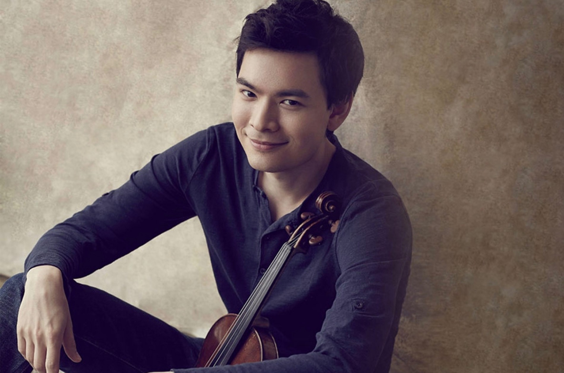 Violinist Stefan Jackiw sitting against wall with violin