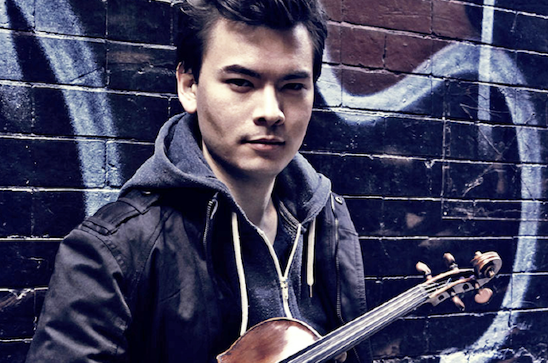 Stefan Jackiw holding a violin in front of a wall of graffiti
