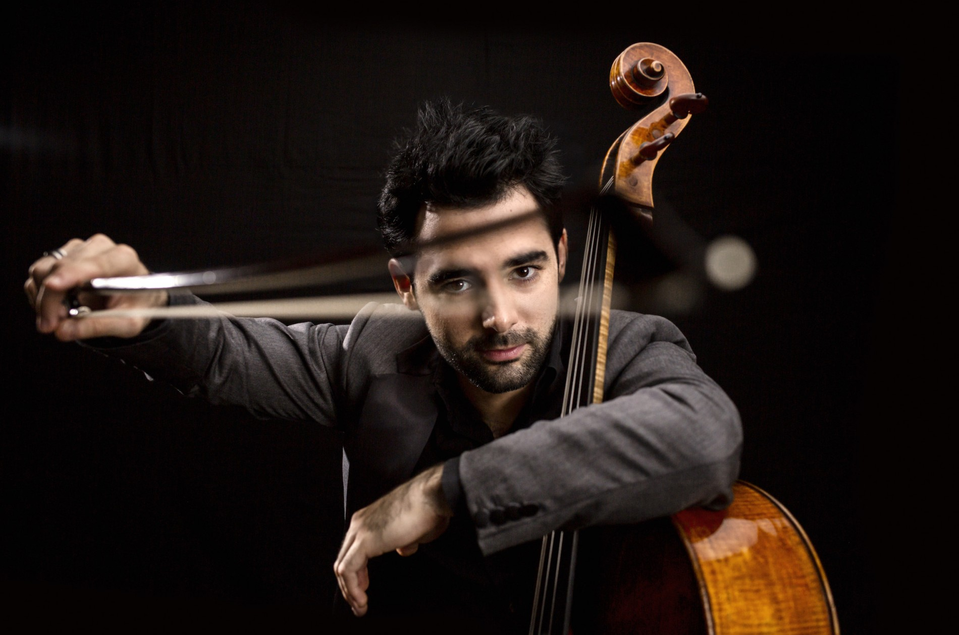 Pablo Ferrández, holding his cello in the crook of his arm and his bow out in front of his face