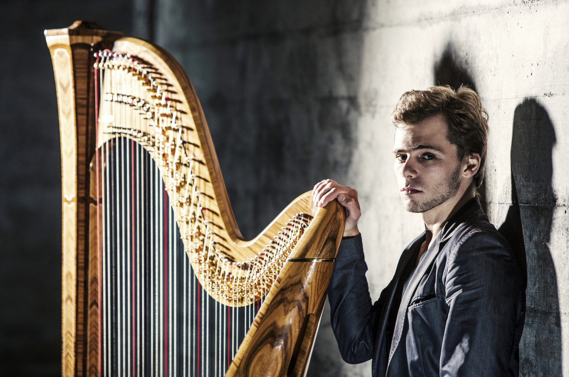 Alexander Boldachev standing with a harp against a brick wall