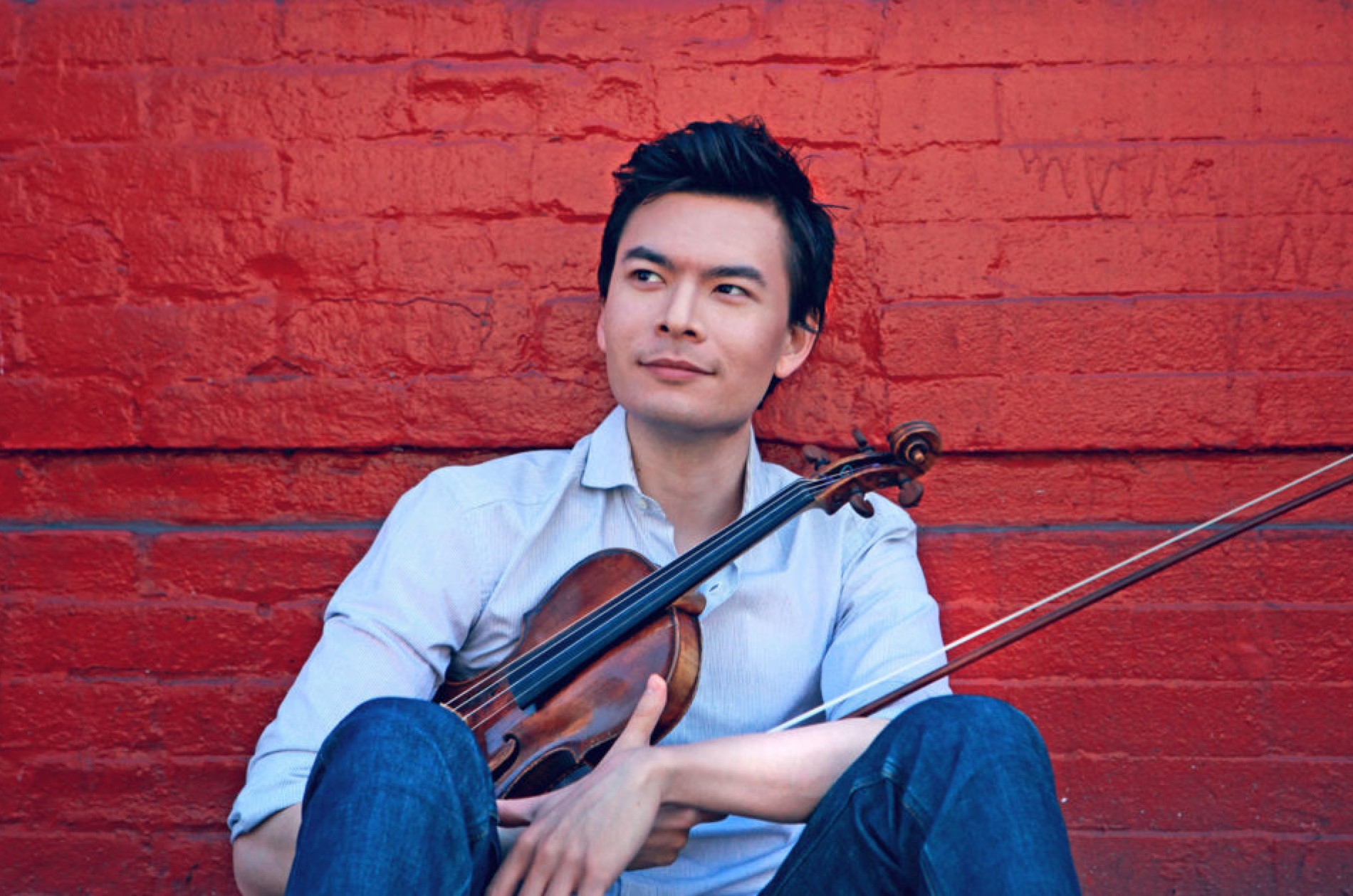 Stefan Jackiw holding a violin while sitting in front of a painted red brick wall