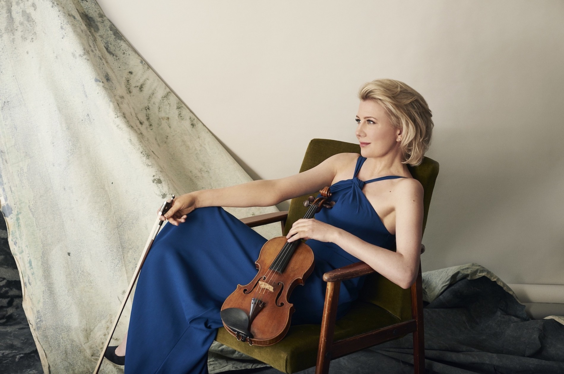 Elina Vähälä seated in a chair and holding a violin