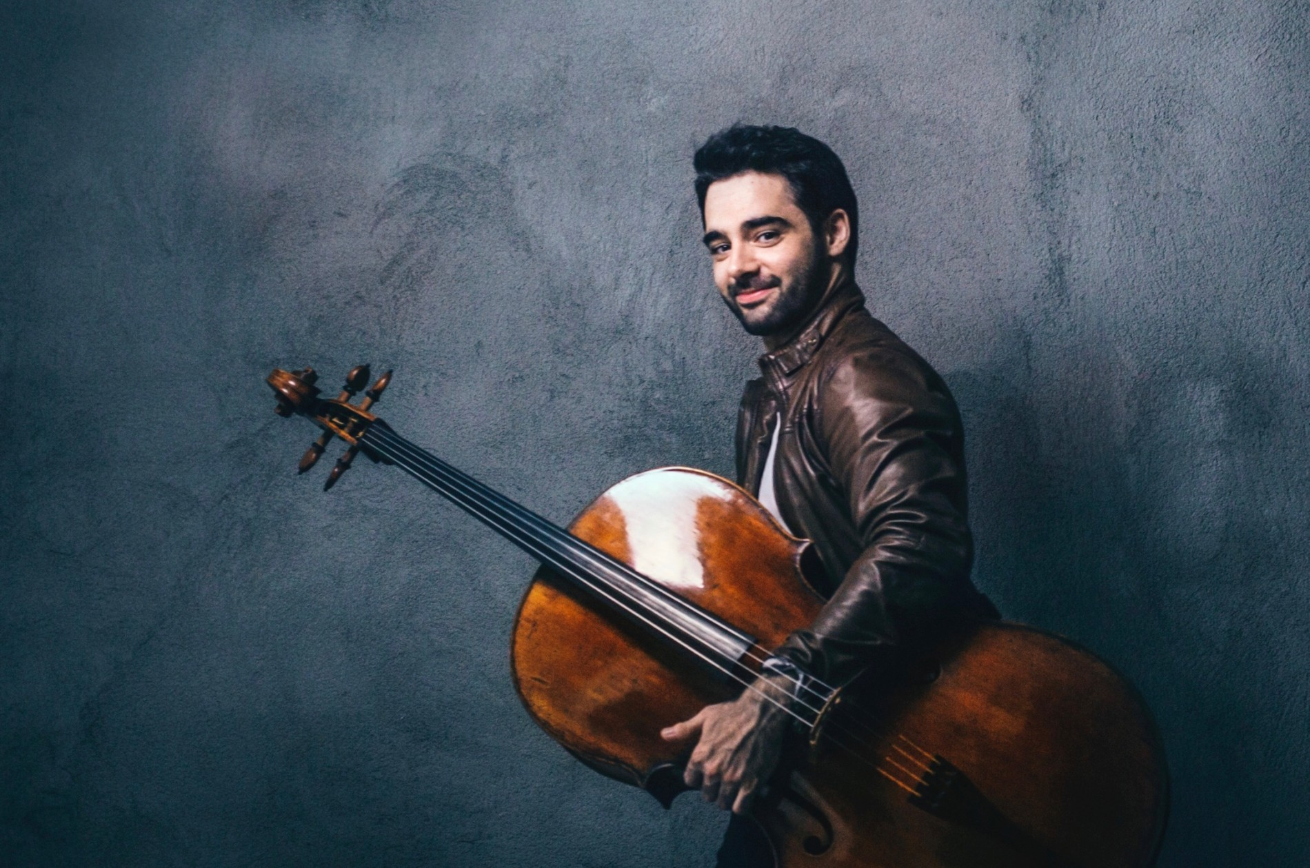 Pablo Ferrández, cellist, holding his instrument in left hand